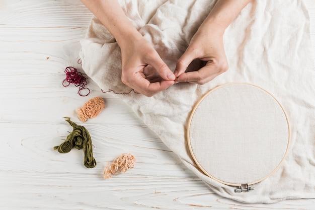 Hand met naald en draad op tambour frame