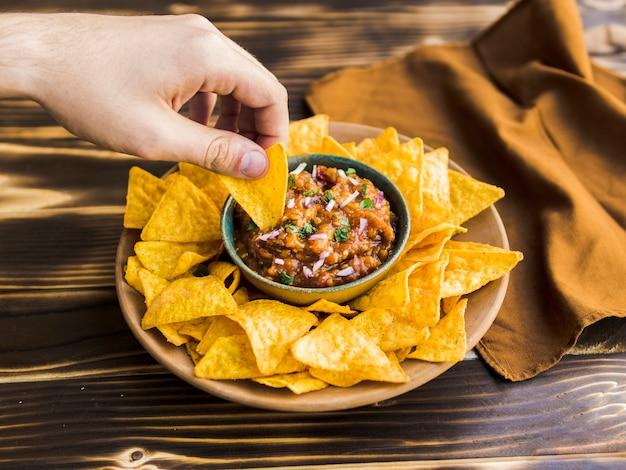 Hand met nacho in kopje garnituur
