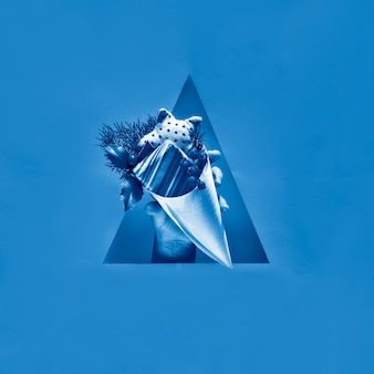 Hand met natuurlijke decoraties en milieuvriendelijk geschenk in multiplex kegel die uit een driehoekig papiergat komt. monochroom blauwe kleur vierkante papieren muur. fijne zero waste wintervakantie!