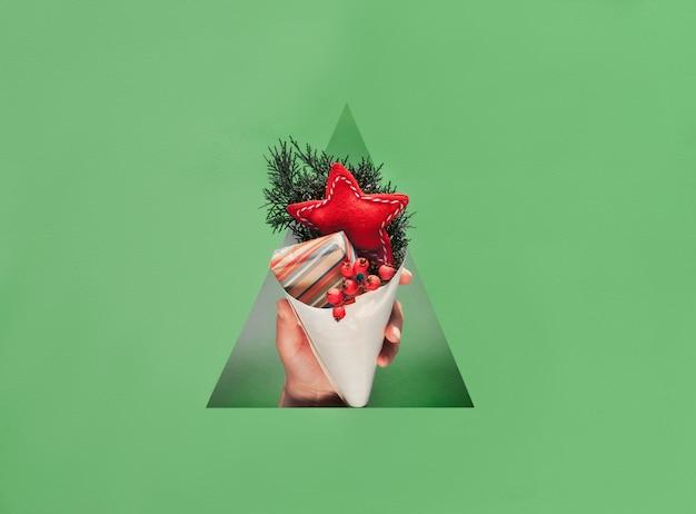 Hand met natuurlijke decoraties, geschenkdoos in gestreept kraftpapier en zacht vilten handgemaakte ster in multiplex kegel in driehoekig papier gat.