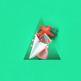 Hand met natuurlijke decoraties, geschenkdoos in kraftpapier en zachte vilten handgemaakte rode ster in multiplex kegel in driehoekig papier gat. gelukkig wintervakantie zonder afval