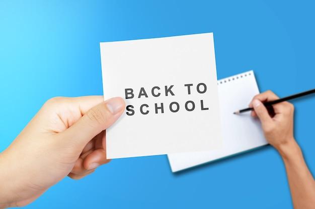 Hand met papier met terug naar school tekst met een gekleurde achtergrond. terug naar school-concept
