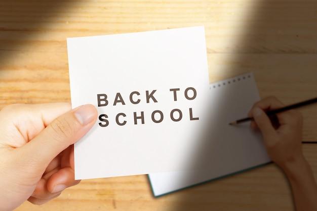Hand met papier met terug naar school tekst met houten achtergrond. terug naar school-concept