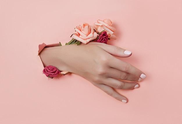 Hand met papieren bloemen en gelakte nagels wordt door een gat in de papieren achtergrond gestoken