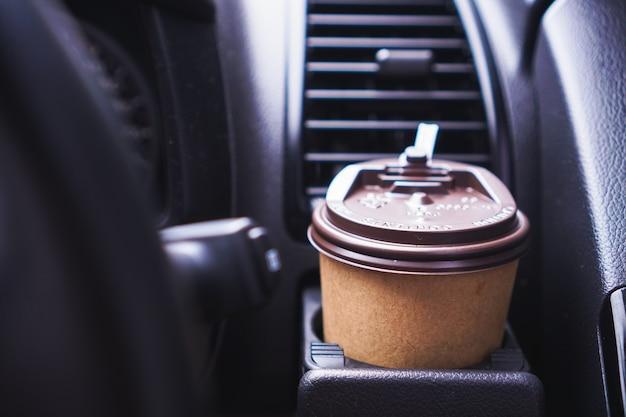 Hand met papieren koffiekopje tijdens het autorijden in de ochtend