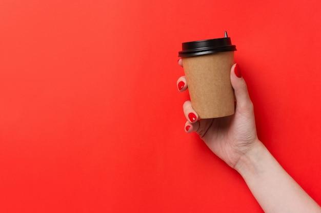 Hand met papieren kopje koffie op rode achtergrond.