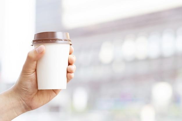 Hand met papieren kopje van take away drinken koffie op natuurlijke ochtendzon.