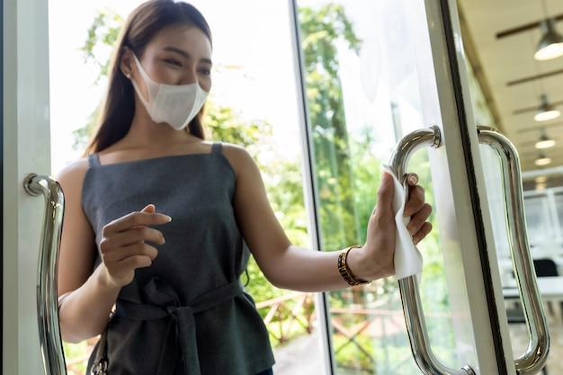 Hand met papieren zakdoekje om restaurantdeur open te duwen.