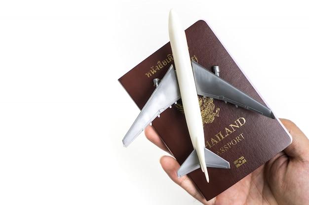 Hand met paspoort en speelgoed vliegtuig voor air zakenreizen concept