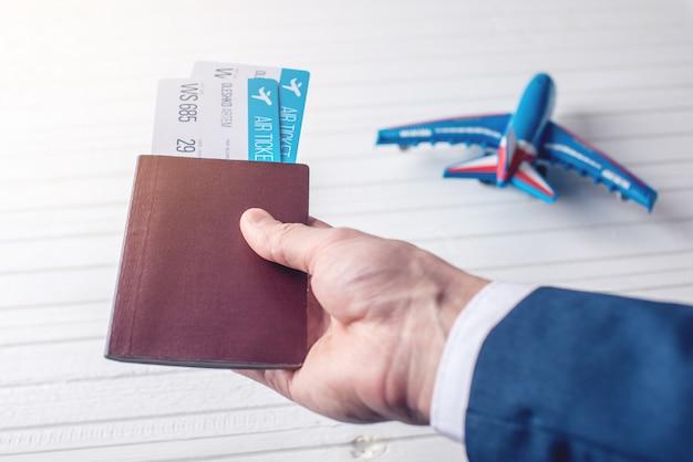 Hand met paspoort met vliegtickets op een witte achtergrond