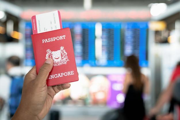 Hand met paspoorten en borading pas in de internationale luchthaven.