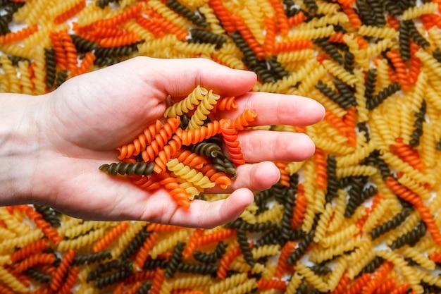 Hand met pasta close-up. horizontaal.