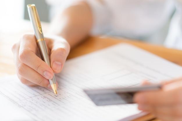 Hand met pen en creditcard over het aanvraagformulier.