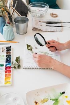 Hand met pen en vergrootglas