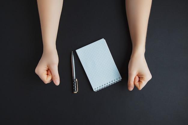 Hand met pen en wit papier, op donkere tafel