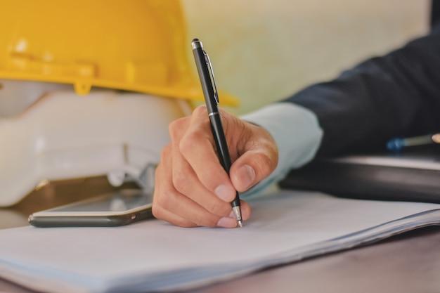 Hand met pen handtekening op document (concept bedrijf, financiën, verzekering)