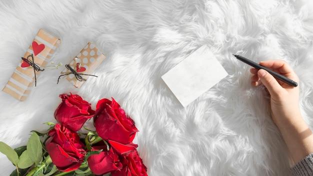 Hand met pen in de buurt van papier, geschenken en verse bloemen op wollen deken