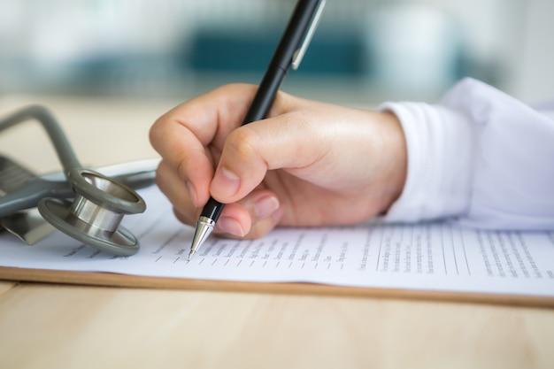 Hand met pen invullen van een document