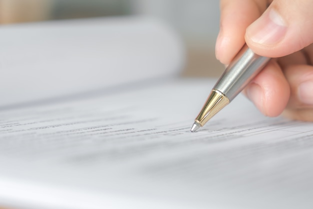 Hand met pen over aanvraagformulier
