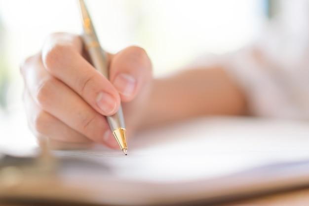Hand met pen over het aanvraagformulier