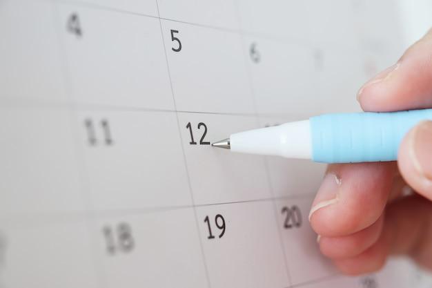 Hand met pen schrijven op kalenderdatum
