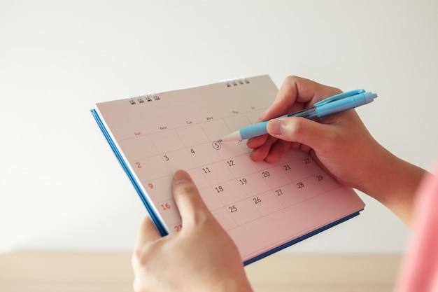 Hand met penteken op 5e op kalenderdatum met blauwe cirkel