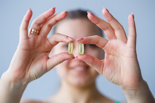 Hand met pillen. de vrouw neemt medicijnen om de immuniteit te verbeteren. dagelijkse norm van vitamines, effectieve preparaten, moderne apotheek voor de gezondheid.