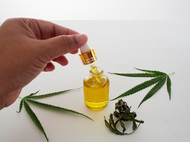 Hand met pipetten en cannabis extract olie.