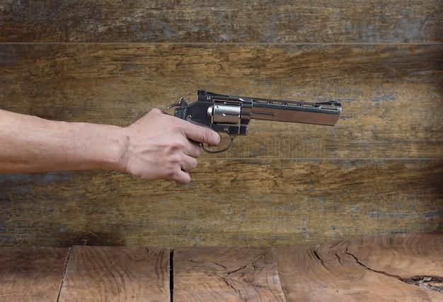 Hand met pistool geïsoleerd op een zwarte achtergrond