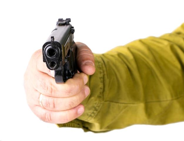 Hand met pistool op wit wordt geïsoleerd dat