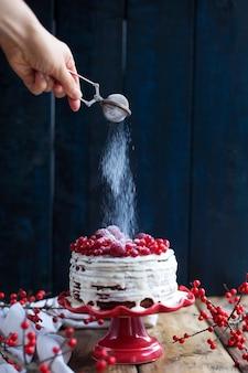 Hand met poeder en witte cake met rode bessen op een zwarte achtergrond