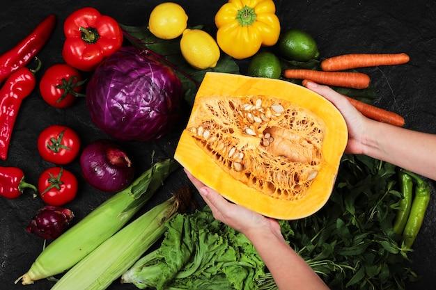 Hand met pompoen en diverse verse groenten op balack tafel.