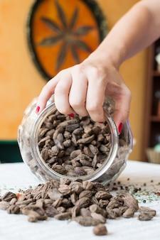 Hand met pot met zwarte kardemom zaden