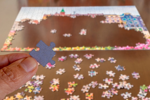 Hand met puzzelstukje, activiteitenconcept tijdens thuisblijven als gevolg van pandemie.