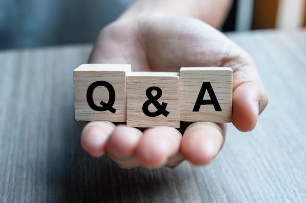 Hand met q&a houten kubusblok