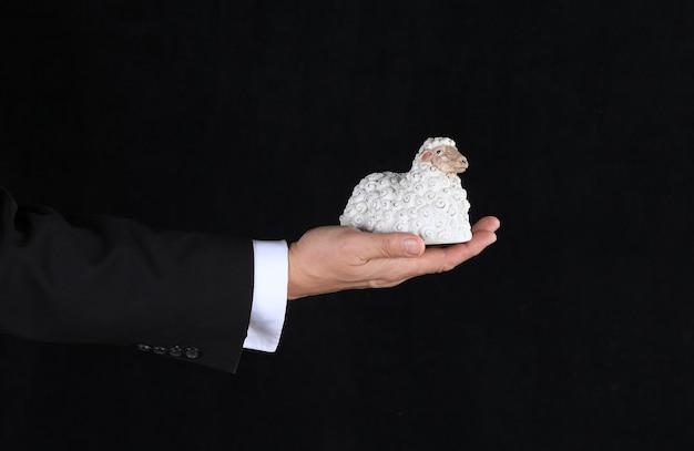 Hand met ram speelgoed op zwarte achtergrond