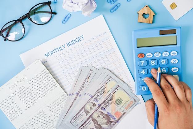 Hand met rekenmachine berekening van de maandelijkse begroting met bankboekje en ons bankbiljet plat lag op blauwe achtergrond