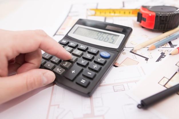 Hand met rekenmachine op de plattegrond van het huis. het concept van een huis renoveren of bouwen.