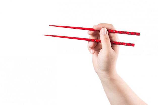 Hand met rode geïsoleerde eetstokjes