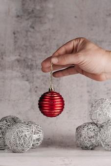Hand met rode kerst bal op zilveren achtergrond