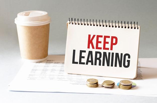 Hand met rode pen cofee cup stick keyboard en witte achtergrond houd leren teken in het notitieblok