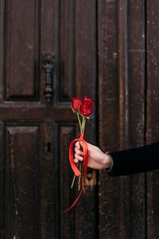 Hand met rode rozen boeket
