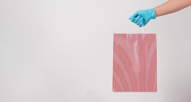 Hand met rode strepen boodschappentas en draag blauwe medische handschoen geïsoleerd op een witte achtergrond.