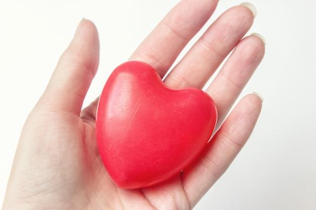 Hand met rood hart, gezondheidszorg, donatie en familieverzekeringsconcept wereldhartgezondheidsdag idee