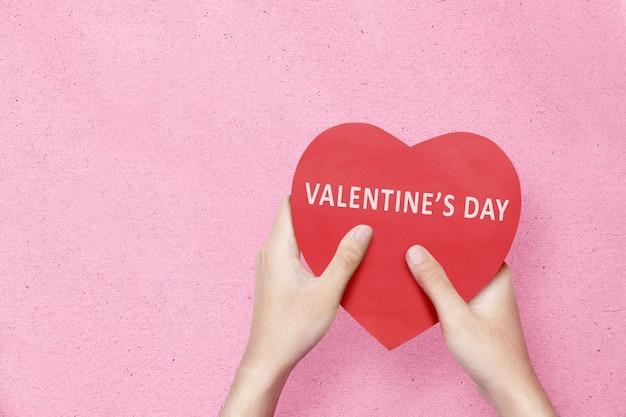 Hand met rood hart met happy valentines day-tekst op een roze muur. valentijnsdag