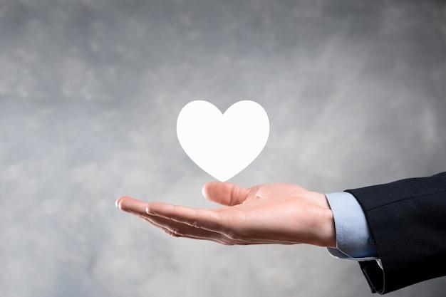Hand met rood hart met wit kruis symbool. wereld kaart achtergrond. gezondheidszorg, ziektekostenverzekering, liefdadigheid en geneeskunde concept. kopieer ruimte.