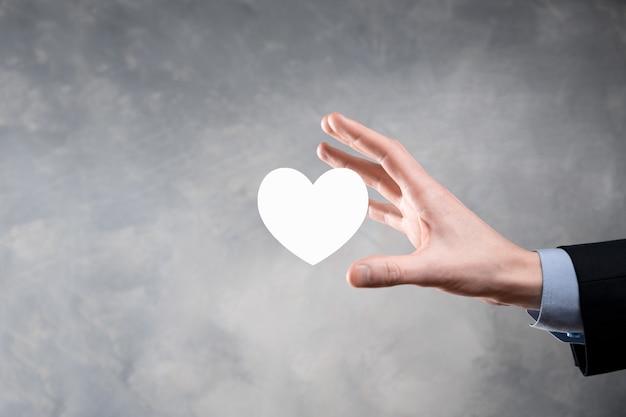 Hand met rood hart met wit kruis symbool. wereldkaart muur. gezondheidszorg, ziektekostenverzekering, liefdadigheid en geneeskunde concept. kopieer ruimte.