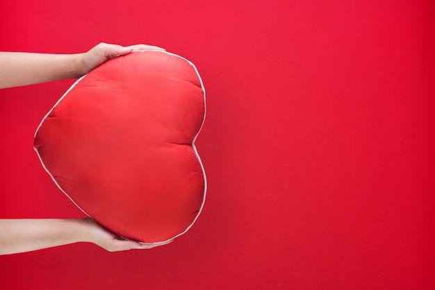 Hand met rood hart op papier achtergrond met kopie ruimte voor liefde bruiloft of valentijnsdag.