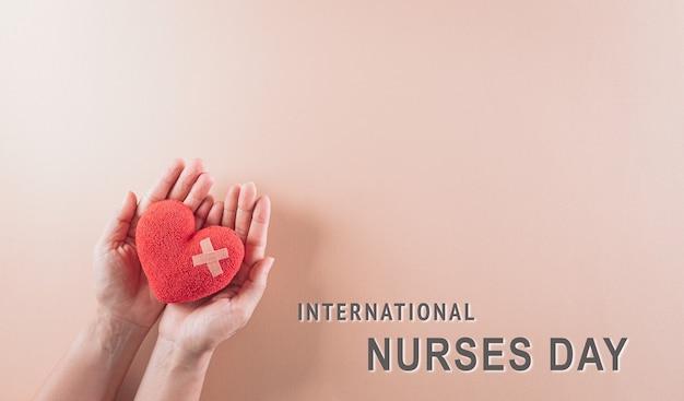 Hand met rood hart op pastel achtergrond met internationale verpleegkundigen dag tekst