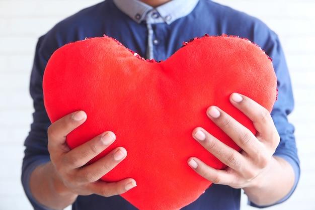 Hand met rood hartsymbool op witte achtergrond
